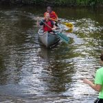 two people canoeing in a river