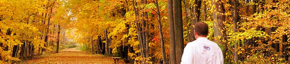 Man Walking Down trail covered with fall colored leaves with a canopy of trees overhead