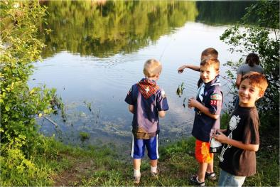 Kids fishing on the shoreline of a lake