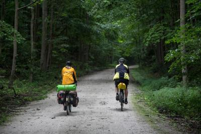 two cyclists on wooded biking trail