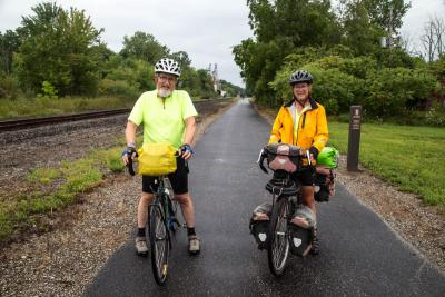 two cyclists on paved trail stopping for a photo