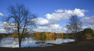 lake with reflection of trees in fall color and blue skies with white clouds