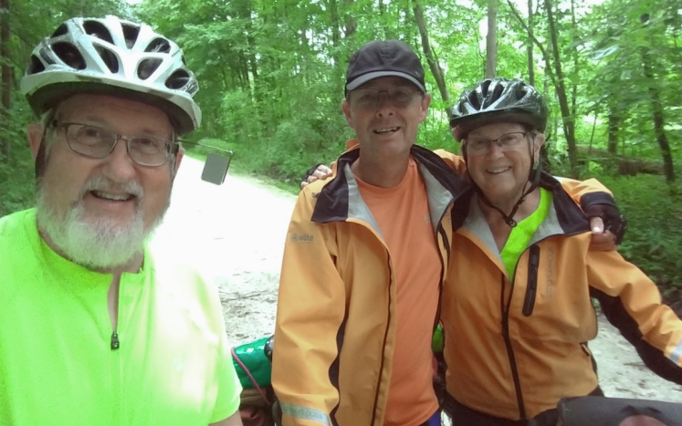 Three cyclists taking a selfie, Male on left with green shirt, Center Male with orange jacket and female with orange jacket